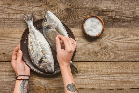 partial view of tattooed woman salting uncooked fish on wooden table Stock Photo