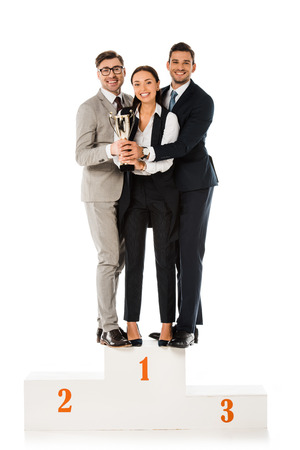business team holding trophy cup while standing on winners podium together isolated on white Banco de Imagens