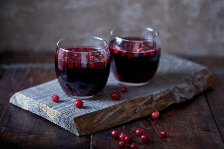 two glasses of tasty mulled wine with cranberries on wooden stand in kitchen Standard-Bild