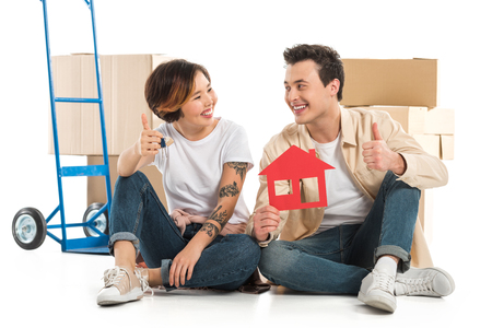 couple showing thumbs up signs and holding house model, moving to new house concept Stok Fotoğraf