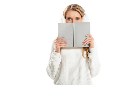 happy girl hiding behind the book isolated on white