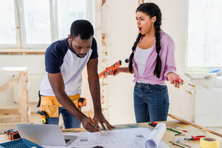 african american man making notes on blueprint at table with laptop while his angry girlfriend yelling at him near during renovation of home Stock Photo - 112467467