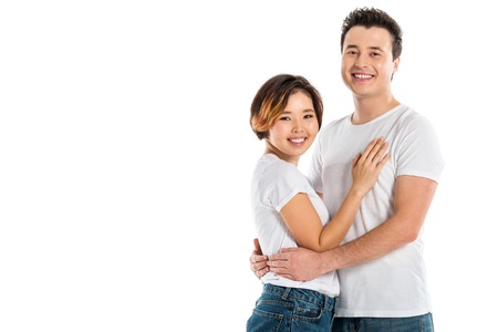 happy couple hugging and looking at camera isolated on white