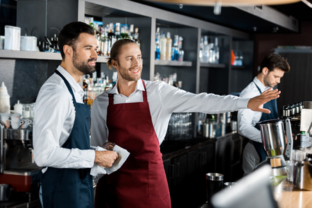 cheerful smiling barmen gesturing at workplace while coworker looking aside