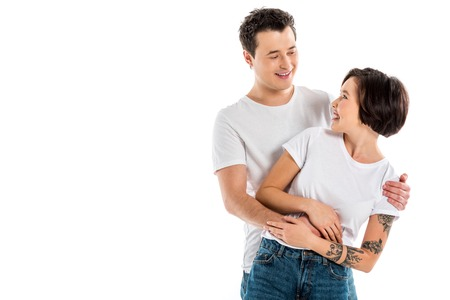smiling couple embracing and looking at each other isolated on white