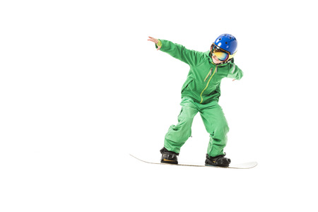 preteen boy in green ski suit, goggles and blue helmet snowboarding isolated on white Stock Photo