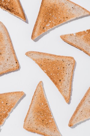 top view of toasts cut in triangles on white surface Stock Photo