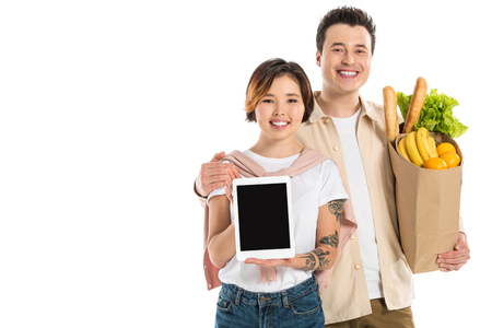 smiling husband holding grocery bag while wife presenting digital tablet with blank screen isolated on white Stok Fotoğraf - 112468909