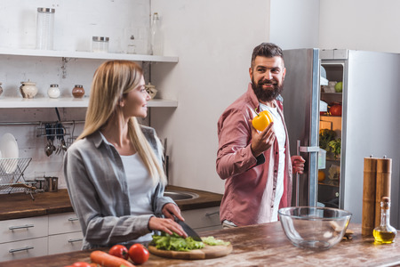 Wife cutting salad leaves and husband standing near refrigerator Banco de Imagens