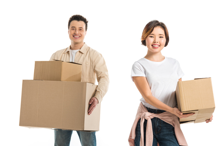 happy couple looking at camera and holding cardboard boxes isolated on white, moving to new house concept Stok Fotoğraf
