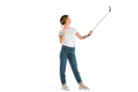 smiling young woman waving, taking selfie on smartphone and using selfie stick isolated on white