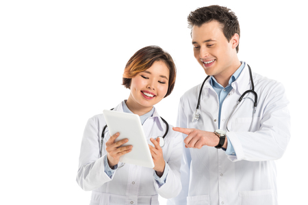 smiling female and male doctors with stethoscopes using digital tablet isolated on white