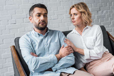 woman talking to depressed husband while sitting on couch after quarrel Stock Photo