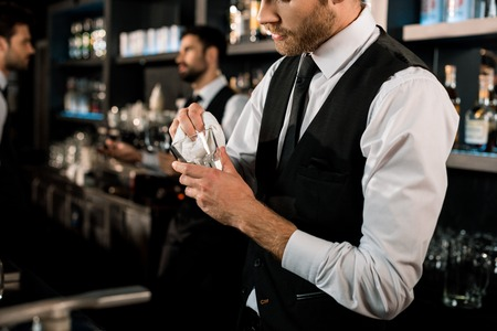 Bartender cleaning glass with white cloth in bar