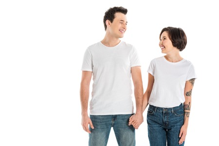 happy couple holding hands and looking at each other isolated on white