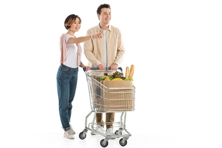 husband with shopping cart full of groceries standing near wife pointing finger isolated on white