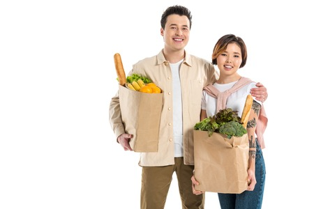 smiling husband and wife holding grocery bags and looking at camera isolated on white Stok Fotoğraf