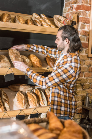 Side view of male seller putting freshly baked bread on wooden shelf Stock Photo
