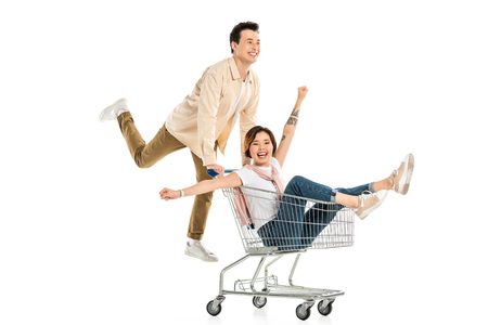 happy husband pushing shopping cart with wife inside isolated on white, couple having fun Stok Fotoğraf