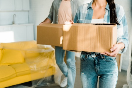 cropped view of husband and wife carrying cardboard boxes and packing for new house, moving concept Reklamní fotografie - 112513535