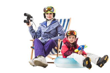 Young woman in ski suit with binoculars in deck chair and preschooler daughter with water gun looking at camera isolated on white