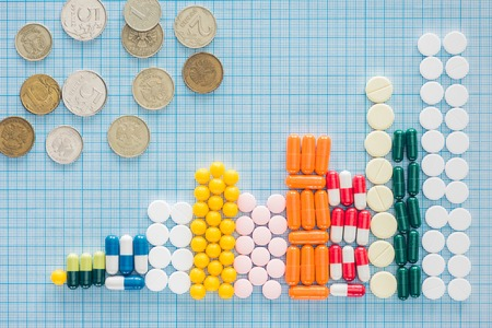 view from above of arranged stacks of colorful pills and russian rubles on blue checkered surface