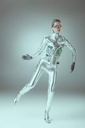full length view of silver woman robot balancing on grey, future technology concept Reklamní fotografie
