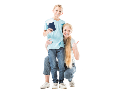 Mother showing thumbs up and son smiling and holding passport isolated on white