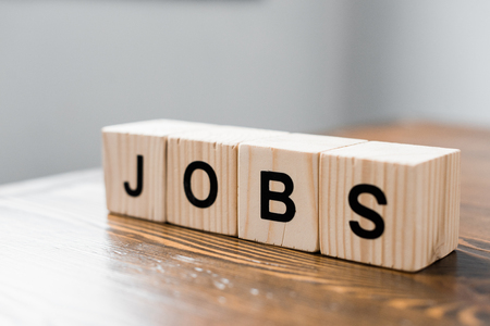 close-up shot of wooden cubes with JOBS sign on table