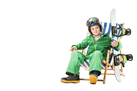 Preteen boy in green ski suit with snowboard sitting in deck chair isolated on white