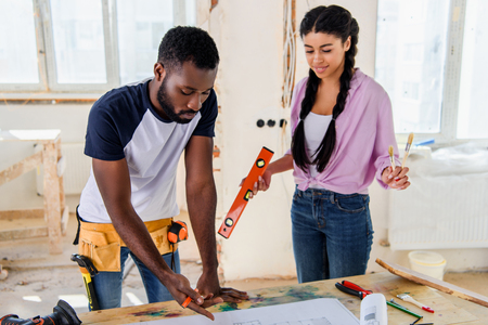 handsome young man pointing at blueprint to attractive girlfriend standing near during renovation of home Stock Photo - 112522296