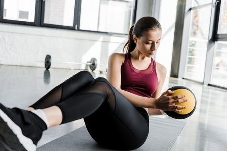 beautiful determined sportswoman working out on abs with medicine ball at sports center