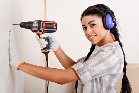 beautiful young woman drilling wall and looking at camera during renovation of home