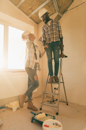 low angle view of man in hard hat and goggles standing power drill on ladder while his girlfriend standing near during renovation of home