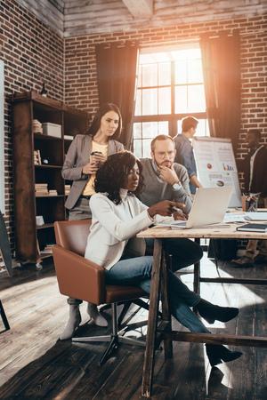 multiethnische Gruppe von Kollegen, die zusammen an einem neuen Projekt in einem modernen Loft-Büro mit Hintergrundbeleuchtung arbeiten Standard-Bild
