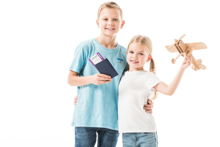 Kids standing with plane model, passport and tickets isolated on white