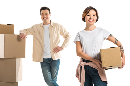 smiling couple looking at camera and holding cardboard boxes isolated on white, moving to new house concept