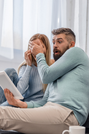 Husband closing eyes of wife and looking on digital tablet 스톡 콘텐츠