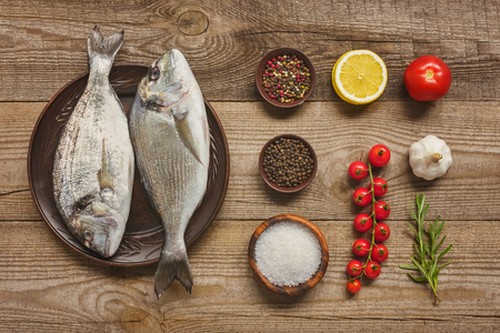 elevated view of plate with uncooked fish near arranged ingredients on wooden table