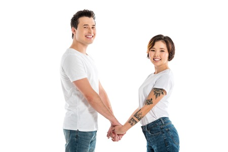 cheerful couple holding hands and looking at camera isolated on white