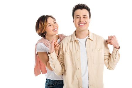 portrait of smiling couple in casual clothes holding hands and looking at camera isolated on white Stok Fotoğraf