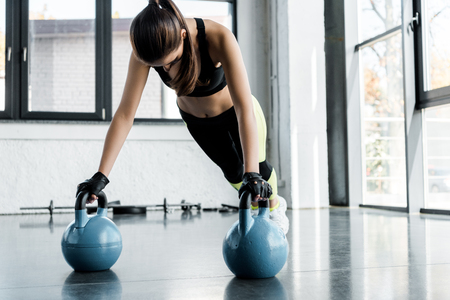 strong sportswoman in weightlifting gloves doing plank exercise on kettlebells at gym