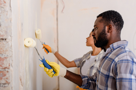 side view of african american couple painting wall by paint rollers at new home Imagens