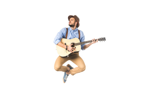 romantic young musician looking away while playing guitar and jumping isolated on white