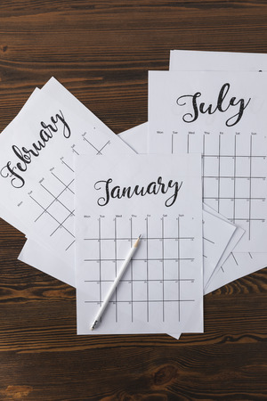 flat lay with arranged calendar papers and pencil on wooden tabletop Stockfoto