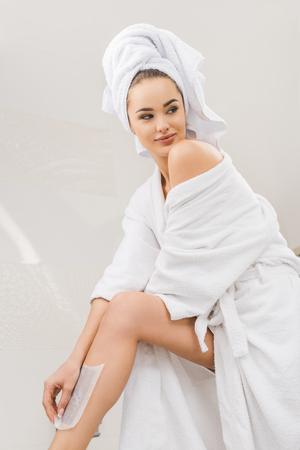 beautiful woman in bathrobe with towel on head doing wax depilation at home Zdjęcie Seryjne