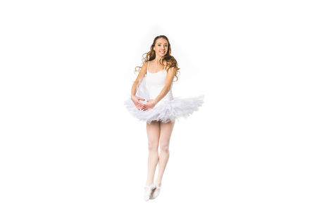 happy young ballerina dancing and smiling at camera isolated on white