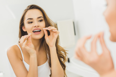 portrait of beautiful woman cleaning teeth with dental floss Archivio Fotografico - 112539971