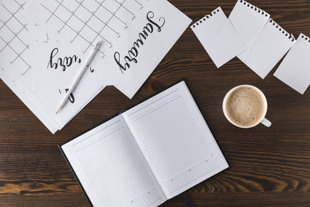 flat lay with empty notebook, calendar and cup of coffee on wooden surface