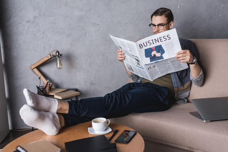 young barefoot businessman reading newspaper on couch